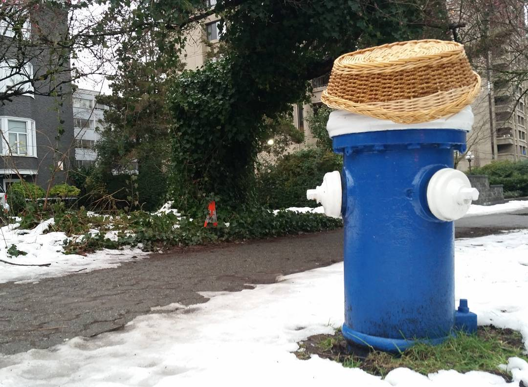 A blue fire hydrant with a straw hat on top of it
