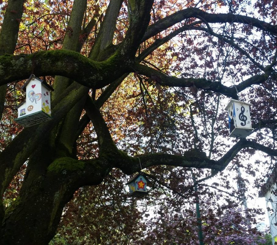 A tree with little decorated birdhouses in it