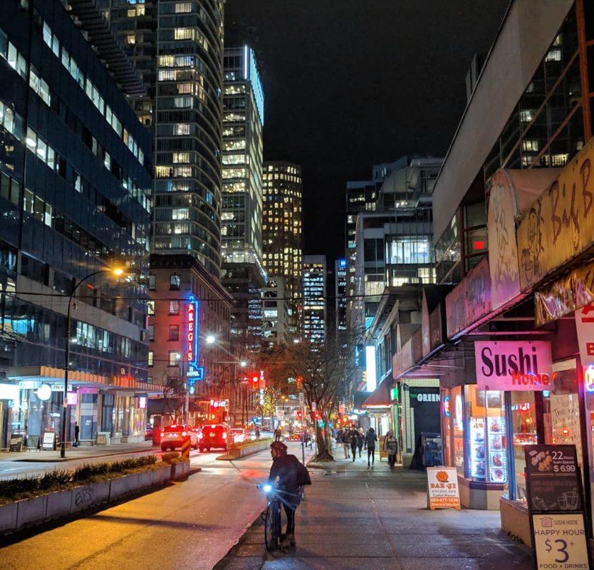 city lights and a guy on a bike