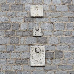 three odd sundials on a wall